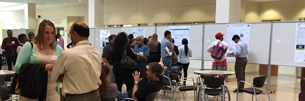 Prof. Nihal Ahmad (foreground right) speaks with graduate student Charlotte Mintie (foreground left) during the poster session in the Health Sciences Learning Center atrium.