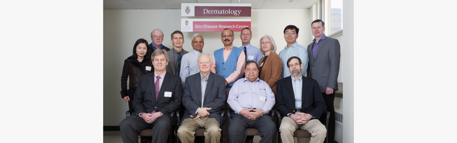 Group photo of the UW core directors and Executive Advisory Board of the UW Skin Disease Research Center. Four men are seated at front, with nine men and women standing behind them.