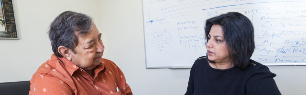 A picture of two researchers, Professor Hasan Mukhtar and Dr. Deeba Syed, talking in an office.