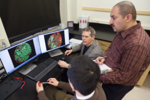 B. Jack Longley, MD, (seated back), Tony Xiao, MD (seated, front), and Numan Al-Rayyan (standing) use the SDRC's advanced imaging software to review six-color-stained slides.